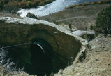View from top of a hill of a canal drainage pipe