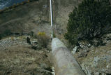 View from above of a pipe going down hill toward canal