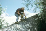 Man cutting pipe