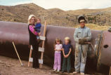 Man with family, standing next to pipe