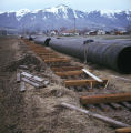 Two sections of pipe, next to make-shift tracks
