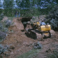 Man plowing through mud in bulldozer
