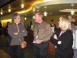 Visitor socializing  with library staff during the opening night reception of the Bells exhibit;