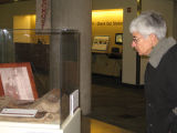 Visitor viewing a Bells exhibit display case;