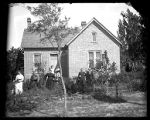 Family gathered in front of brick home;