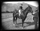 Unidentified jockey on a horse at a racetrack;