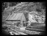 Miners at a log cabin with timbers at the Baker silver mine;