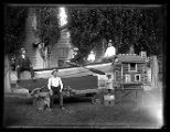 Four men and some children sitting on an early rowboat trailer;
