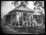 Adobe brick home with a family gathered in front;