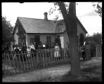 Large family gathered before their small adobe brick home with picket fence and hedges (1 of 2);