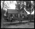 Large family gathered before their small adobe brick home with picket fence and hedges (2 of 2);