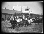 Horse-drawn parade float near a bowery and schoolhouse;