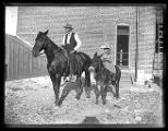A man and his daughter riding horses behind a building in downtown Brigham City;