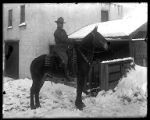 Henry Seeger of Brigham City, astride a horse outside a stable;