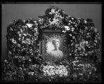 Funeral flower spray with portrait of unidentified woman (1 of 2);
