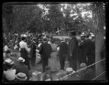 People gathered for a large celebration in a park, probably in Brigham City, possibly for Peach...