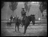 Man dressed in chaps and other cowboy attire, riding a horse, on the streets of Brigham City (1 of...