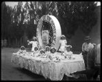 Horse-drawn parade float with young girls dressed in white sitting around the Seal of the State of...