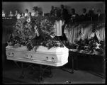 White casket decorated with flowers at a funeral in Brigham City;