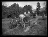 Man oiling his horse-drawn grain harvester;