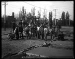 Crew with freshly-poured concrete sidewalk and cement mixer;