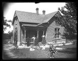 Family gathered in front of their brick home, probably Brigham City, Utah;