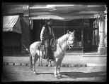 R. Burrell on horseback in cowboy attire before Compton Studio;