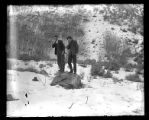 Two young men holding their noses while standing on a rock, a dead rabbit and rifle at their feet;