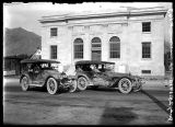Two automobiles parked in front of the Federal Building (1 of 2);