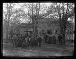 Family gathered in front of their adobe brick home;