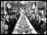 People sitting at a long dinner table decorated for a holiday with American flags;