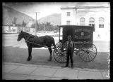 Man standing next to a horse-drawn Grand Union Tea Company wagon;