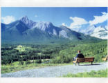 Man sitting on a bench overlooking the valley;
