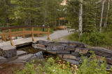 Bridge over stream on walkway through forest in Kananaskis, Alberta, Canada;
