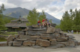 Children sitting on large stack of rocks used for a waterfall at Kananaskis Village, Alberta,...