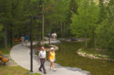 People on walkway by a stream at Kananaskis Village, Alberta, Canada;