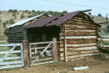 Log outbuilding with log animal shelter attached, located at the William Ballingham complex...