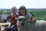 Toni Tanner with unidentified girl and sheep on 4-H float in Fourth of July Parade (GCCS_CTC024_6)