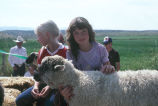 Toni Tanner with unidentified girl and sheep on 4-H float in Fourth of July Parade (GCCS_CTC024_7)