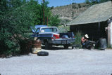 Unidentified man fixes tire at the side of the Grouses Creek, Utah, Co-op (GCCS_CHC001_18)