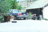 Unidentified man fixes tire at the side of the Grouses Creek, Utah, Co-op (GCCS_CHC001_19)