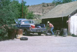 Unidentified man fixes tire at the side of the Grouses Creek, Utah, Co-op (GCCS_CHC001_20)