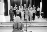 A chorus of school children led by a teacher (GCCS_BCF231196_10_23)