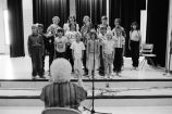 A chorus of school children led by a teacher (GCCS_BCF231196_10_24)