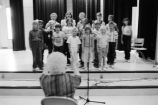 A chorus of school children led by a teacher (GCCS_BCF231196_10_25)