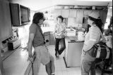 Tom Carter, Kathleen Tanner, and Carol Edison in the Tanner kitchen after dinner...