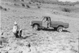 Max Tanner stooped near  a truck during tour in mountain above Death Valley (GCCS_BHC25554_10)