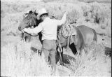Milt Oman preparing to mount a horse near an old stage stop in Emigrant Canyon, Idaho...