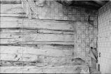 Detail of Warburton log house interior showing log walls and wallpaper (GCCS_BTC90105_35)