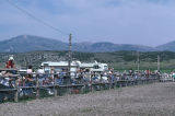 Rodeo spectators lined up against fence during 4th of July celebration (GCCS_CCE018_6)